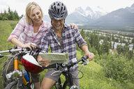 Couple on mountain bikes reading map on hillside - HEROF02062