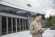 Businesswoman using digital tablet outside office building - HEROF02272