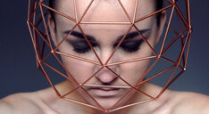 Head shot of a young woman wearing a golden cage around her face - INGF11349