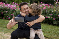 Happy father and son on taking a selfie in park - MAUF02072