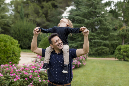 Happy father carrying son on shoulders in park - MAUF02078
