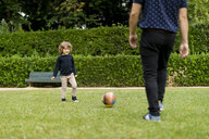 Father and son playing football in park - MAUF02081
