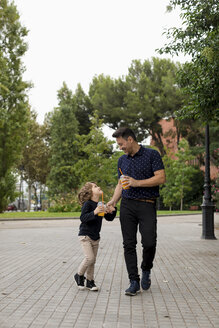 Happy father and son walking hand in hand with soft drinks - MAUF02087