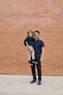 Portrait of smiling father carrying son at brick wall - MAUF02090