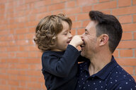 Playful father and son at brick wall - MAUF02093