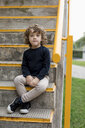 Portrait of boy sitting on stairs - MAUF02096