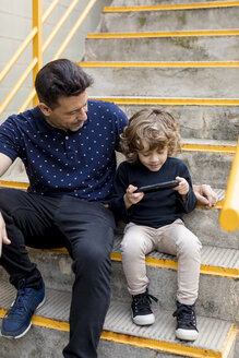 Father watching son playing with handheld game console - MAUF02099