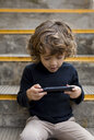 Boy sitting on stairs playing with handheld game console - MAUF02102