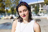 Portrait of smiling young woman with earbuds in the city - MGIF00261