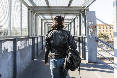 Rear view of young woman walking on a bridge - MGIF00276