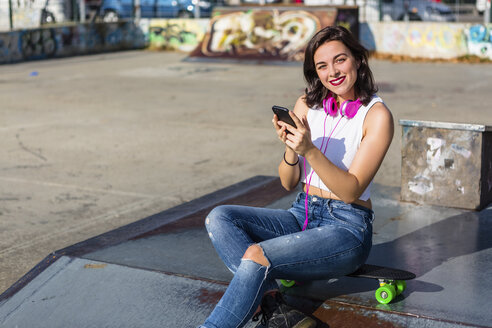 Portrait of smiling young woman with headphones and cell phone at a skatepark - MGIF00279