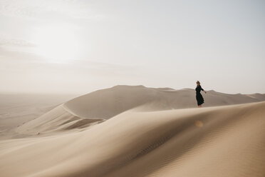 Namibia, Namib, black dressed woman standing on desert dune - LHPF00259