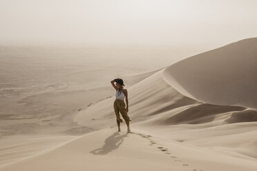 Namibia, Namib, woman standing on desert dune looking at view - LHPF00262