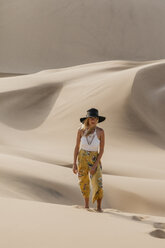 Namibia, Namib, fashionable young woman standing on desert dune - LHPF00265