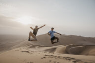 Namibia, Namib, two friends jumping in the air on desert dune - LHPF00271