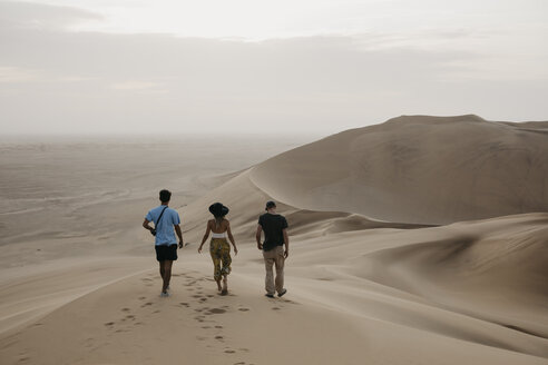 Namibia, Namib, back view of three friends walking side by side on desert dune - LHPF00274