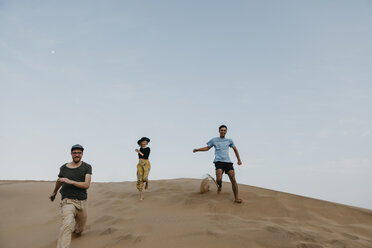Namibia, Namib, three friends running down desert dune having fun - LHPF00277