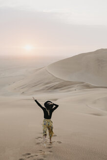 Namibia, Namib, back view of fashionable woman jumping on desert dune - LHPF00283
