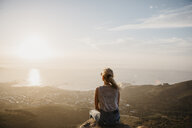 South Africa, Cape Town, Kloof Nek, woman sitting on rock at sunset - LHPF00289