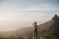 South Africa, Cape Town, Kloof Nek, woman standing on rock at sunset - LHPF00292