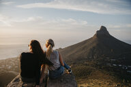 South Africa, Cape Town, Kloof Nek, two women sitting on rock at sunset - LHPF00295