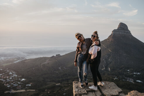 South Africa, Cape Town, Kloof Nek, portrait of two happy women standing on rock at sunset - LHPF00301