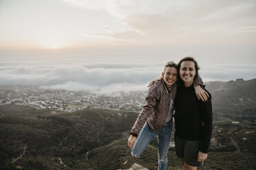 South Africa, Cape Town, Kloof Nek, portrait of two happy women embracing at sunset - LHPF00304