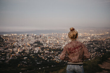 South Africa, Cape Town, Kloof Nek, woman woman looking at cityscape at sunset - LHPF00310
