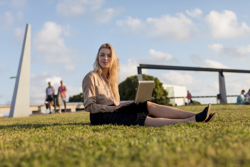 Young businesswoman sitting on a meadow using laptop - MAUF02114