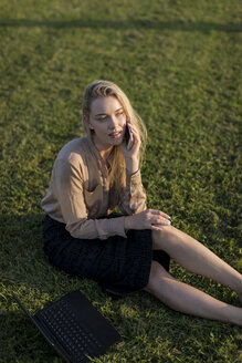 Young businesswoman on cell phone on a meadow - MAUF02117