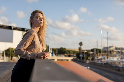 Beautiful young businesswoman with cell phone at the waterfront - MAUF02120