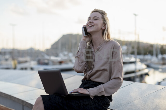 Happy young businesswoman using cell phone and laptop at the waterfront - MAUF02126 - Mauro Grigollo/Westend61