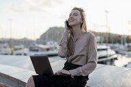 Happy young businesswoman using cell phone and laptop at the waterfront - MAUF02126