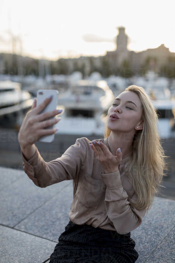 Young woman taking a selfie and blowing a kiss at the waterfront - MAUF02129 - Mauro Grigollo/Westend61