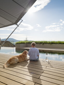Senior woman sitting with dog at the poolside - LAF02204