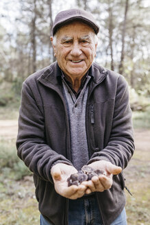 Portrait of smiling senior man showing found mushrooms - JRFF02243