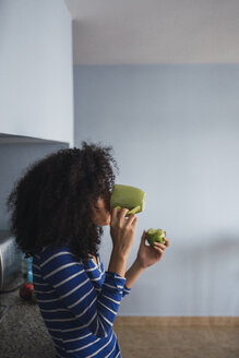 Young woman drinking coffee and eating an apple in her kitchen - KKAF03079