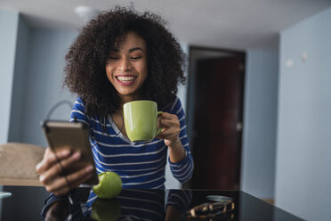 Portrait of happy young woman with coffee mug while looking at cell phone - KKAF03085