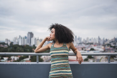 Panama, Panama City, pensive young woman on balcony looking at distance - KKAF03097