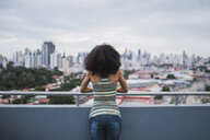 Panama, Panama City, back view of  young woman standing on balcony looking at view - KKAF03100