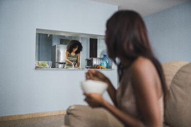 Woman watching her friend working in the kitchen - KKAF03106