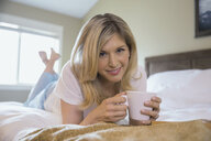 Portrait of woman drinking coffee on bed - HEROF02324