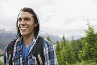 Smiling man in hoody near mountains - HEROF02348