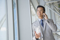 Businessman talking on cell phone at window - HEROF02543