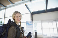 Portrait of smiling woman with backpack in airport - HEROF02645