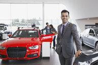 Portrait of confident salesman in car dealership showroom - HEROF02663
