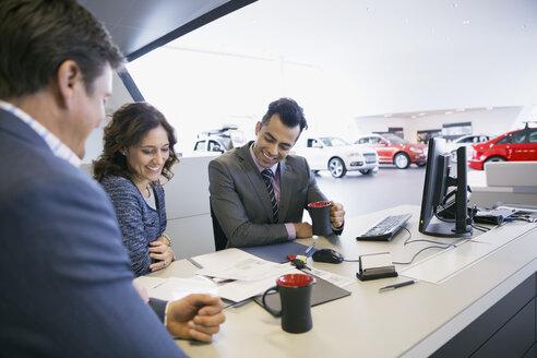 Salesman and couple finalizing paperwork in car dealership - HEROF02666