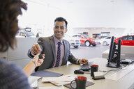 Salesman giving keys to woman in car dealership - HEROF02672