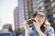 Portrait of smiling woman with camera in city - HEROF02678