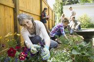 Multi-generation family planting flowers in garden - HEROF02705